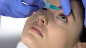 Medique a medicina nos olhos pacientes, controle do gotejamento da visão, seca do globo ocular fotos de stock royalty free