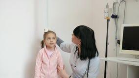 Medique medidas do crescimento do paciente, criança na nomeação do ` s do doutor, trabalhos da enfermeira no hospital, criança do video estoque