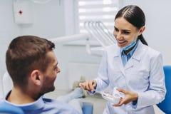 Medique mostrando ao paciente como escovar os dentes no modelo das maxilas fotos de stock