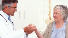 Medique mostrando ao paciente como exercitar a mão ferida video estoque