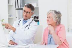 Medique mostrar relatórios ao paciente superior no computador Foto de Stock
