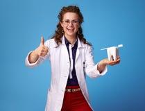 Medique a mulher que mostra os polegares acima e um dente e uma escova de dentes Fotografia de Stock Royalty Free