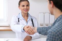 Medique a mulher que sorri ao agitar as mãos com seu paciente masculino Conceito da medicina e da confiança fotografia de stock