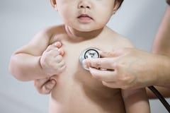 Medique o bebê asiático de exame e escute seu batimento cardíaco imagem de stock