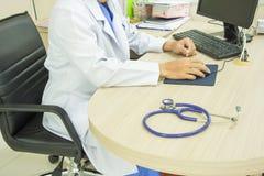 Medique o computador e o stetoscope do uso na mesa imagens de stock royalty free