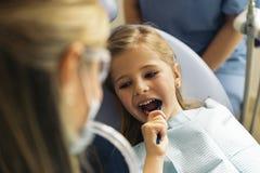 Medique o dentista que ensina uma criança escovar os dentes fotos de stock