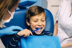 Medique o dentista que ensina uma criança escovar os dentes foto de stock