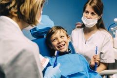 Medique o dentista que ensina uma criança escovar os dentes fotografia de stock