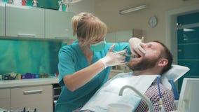 Medique o dentista que faz uma injeção do anestésico local nas gomas vídeos de arquivo