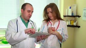 Medique o homem e a mulher da equipe que discutem olhando a agitação do tablet pc e da mão vídeos de arquivo