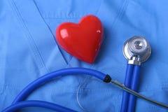 Medique o revestimento com estetoscópio médico e o coração vermelho na mesa imagens de stock royalty free
