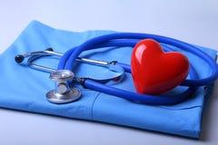 Medique o revestimento com estetoscópio médico e o coração vermelho na mesa fotografia de stock