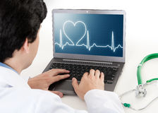 Medique o trabalho no portátil com ekg do ritmo do coração na tela Fotos de Stock