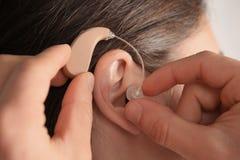 Medique a orelha paciente do ` s de Putting Hearing Aid dentro - fotografia de stock