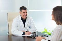 Medique a mulher do homem e do paciente na fala do escritório do hospital foto de stock
