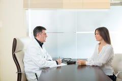 Medique a mulher do homem e do paciente na fala do escritório do hospital fotografia de stock royalty free