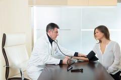 Medique o homem que verifica o punho da pressão sanguínea no paciente da mulher Fotografia de Stock