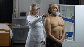 Medique a parte traseira paciente auscultating do ` s na clínica vídeos de arquivo