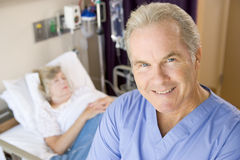 Medique Standing e sorriso no quarto dos pacientes Imagens de Stock Royalty Free