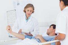 Medique a tomada da pressão sanguínea do paciente masculino imagem de stock royalty free