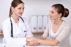 Medique a tranquilidade de seu paciente fêmea ao sentar-se na mesa Conceito da medicina, da ajuda e dos cuidados médicos Foto de Stock