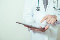 Medique usando uma tabuleta digital no fundo branco Foto de Stock Royalty Free