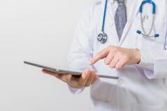 Medique usando uma tabuleta digital no fundo branco Fotos de Stock Royalty Free