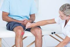 Medique a verificação de reflexos do joelho de seu paciente Imagem de Stock