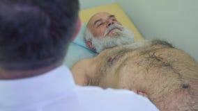 Medique a verificação do abdômen do homem maduro com o instrumento do ultrassom vídeos de arquivo