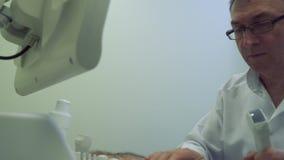 Medique a verificação o abdômen do homem maduro com equipamento do ultrassom video estoque