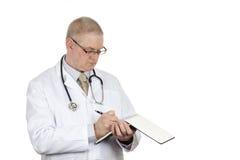 Medique vidros vestindo e escrita do estetoscópio em seu bloco de notas Imagem de Stock Royalty Free