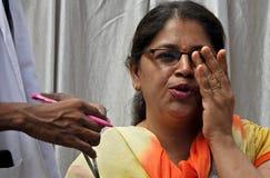 Medique a vista do teste do olho da mulher indiana e leitura e carta de fechamento, em um acampamento médico foto de stock royalty free