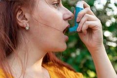 MEDISCH concept Jonge vrouw die astmainhaleertoestel met behulp van royalty-vrije stock foto's