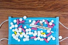 Medisch masker, kwikthermometer en koude geneeskunde - close-up op de lijst Middelen van bescherming tegen het koude en griepseiz stock foto