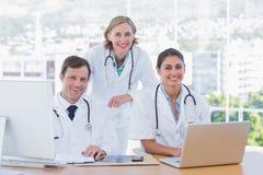Medisch personeel die aan laptop en een computer werken Stock Foto