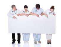Medisch personeel die een witte banner steunen Royalty-vrije Stock Foto