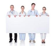 Medisch personeel die een witte banner steunen Stock Afbeelding