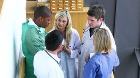 Medisch team die in de treden van een het ziekenhuislengte spreken stock footage