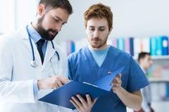 Medisch team die een geduldige testresultaten controleren van ` s stock afbeelding