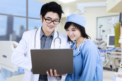Medisch team die laptop computer met behulp van Stock Foto