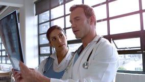 Medisch team die röntgenstraal samen bekijken stock videobeelden