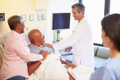 Medisch Team Meeting With Senior Couple in het Ziekenhuiszaal stock afbeelding