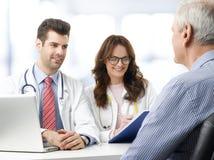Medisch team met bejaarde patiënt Stock Foto's