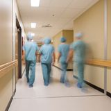 Medisch Team Walking In Hospital Corridor stock afbeelding