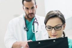 Medisch teamarbeiders die een medisch rapport onderzoeken stock foto