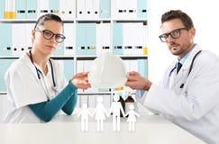 Medisch ziektekostenverzekeringconcept, artsenhanden met familiepictogram Royalty-vrije Stock Foto's