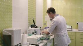 Medische ambtenaar drie in laboratoriumlagen in het laboratorium, die materiaal voor procedures voorbereiden stock video