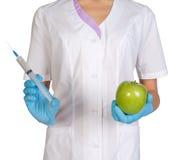 Medische arbeider die een spuitinjectie en groene appelen houden Royalty-vrije Stock Foto's
