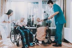 Medische arbeiders Debatteer met Bejaard Paar royalty-vrije stock foto