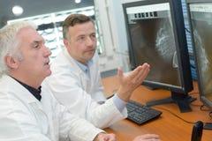 Medische arbeiders die resultaten op het computerscherm bekijken stock foto's